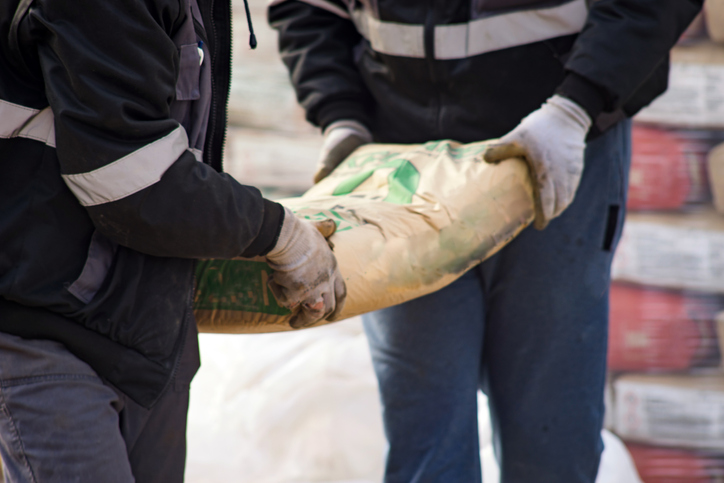 Two construction workers carry a bag of cement midsection close up at the warehouse