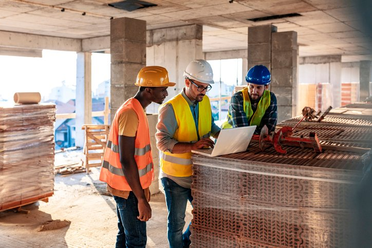 Engineer, architect and business man working on the engineering project at construction site. House building concept. Photo of young male architect engineer using laptop computer.