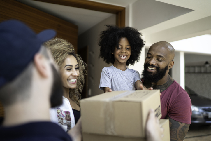 Family receiving a delivery from the mailman