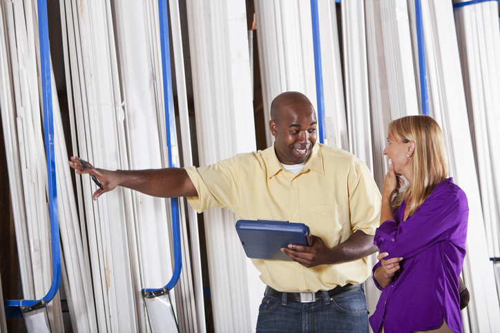 African American worker (20s) in building supply or hardware store helping female customer (40s) in lumber aisle.