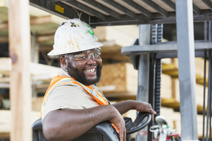 A mid adult African-American man driving a forklift in a lumberyard. He is looking over his shoulder, smiling at the camera, wearing protective clothing - hardhat, safety glasses and reflective vest.